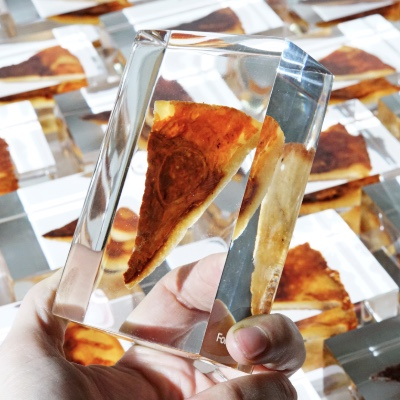 A piece of pizza, encased in acrylic, held up to the camera by a human hand.