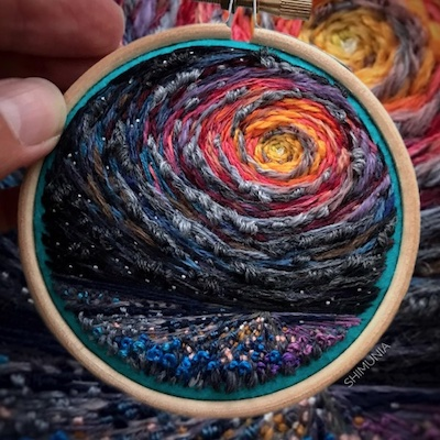 An embroidery piece showing a beautiful, colorful landscape and sunset.