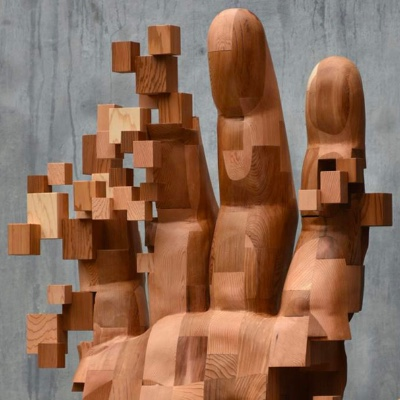 A pixelated hand carved out of wood.