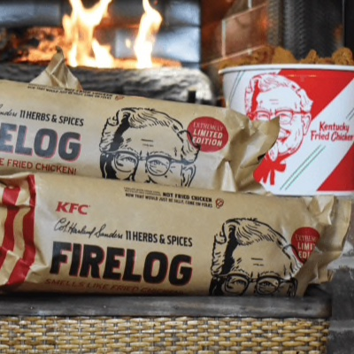 A stack of KFC 11 Herbs & Spices Firelog and a bucket of KFC fried chicken in front of a fireplace.