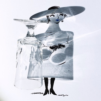 A glass laying sideways, viewed from the top down, casting a shadow.  Inside and around the shadow a things have been drawn, such as a face, hands, and legs, to give the shadow the form of a lady.