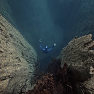 Guillaume Néry underwater near some interesting rock formations.