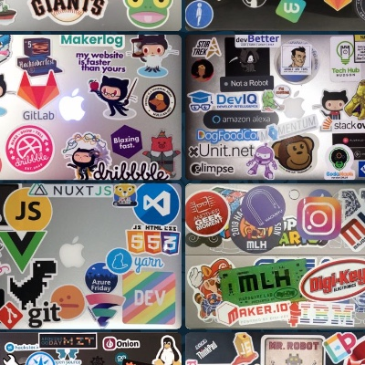 Multiple laptop lids covered in stickers.