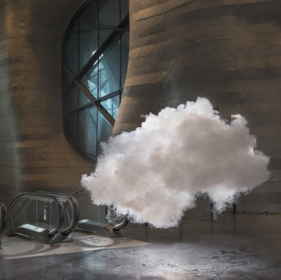 A cloud floating inside a building near an escalator.