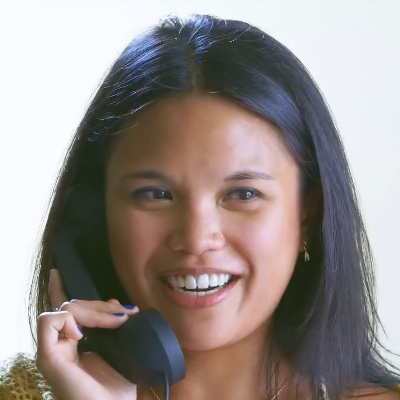 A woman holding a phone and smiling.