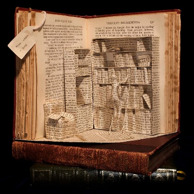 A book, open, standing up vertically, with a library scene inside sculpted using its own pages.